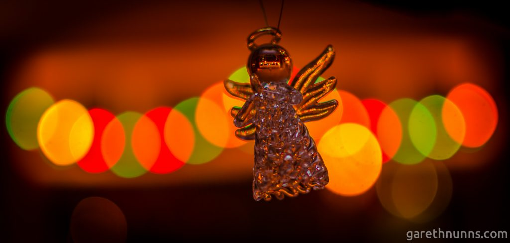 Christmas tree angel with blurred Christmas lights behind