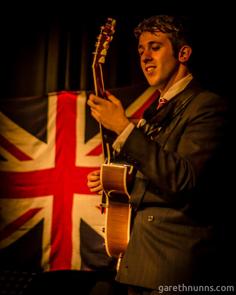 Man playing guitar in front of Union Jack flag
