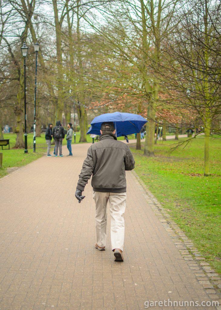 Man walking through Christ's Pieces in the rain in Cambridge