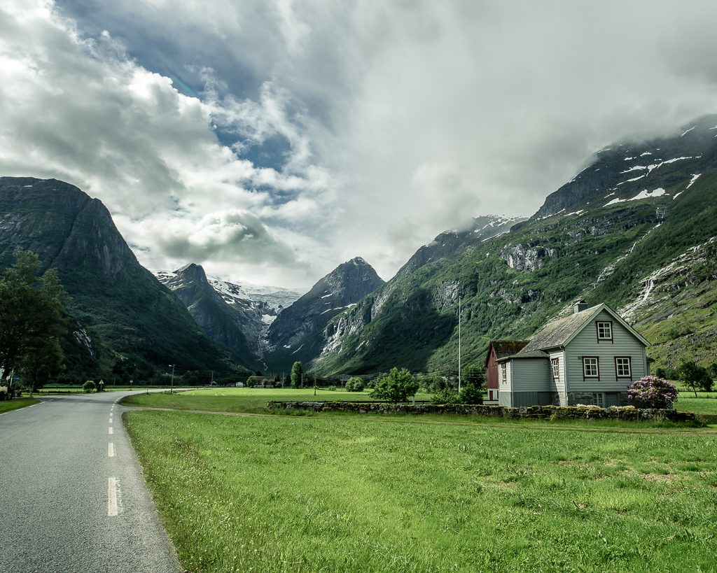 Isolated Norwegian house in a fjord between Olden and Briksdalsbreen on an empty road